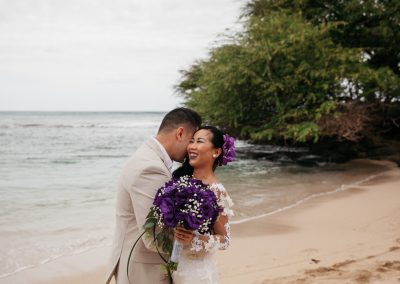 Nhu smiling on the beach while being hugged by her husband