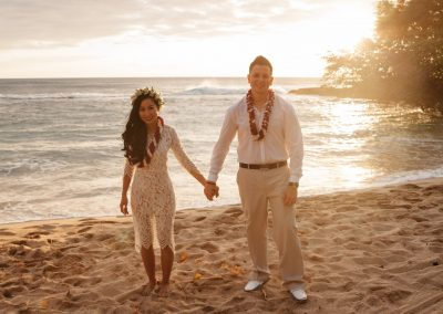 Nhu and her husband holding hands on a beach while wearing their wedding clothes