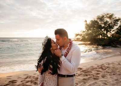 Nhu and her husband standing on a beach in their wedding clothes