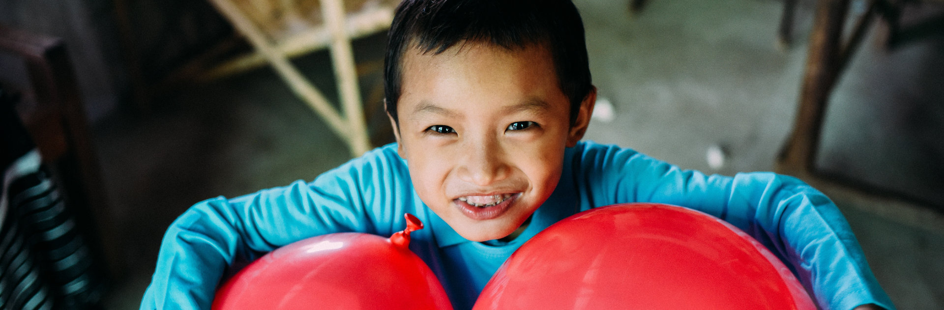 A boy holding two red balloons
