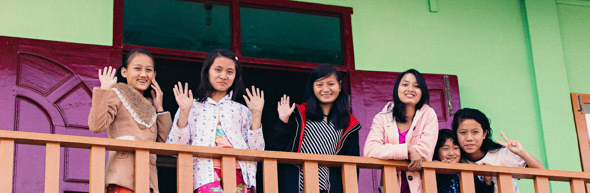 Girls waving on a balcony